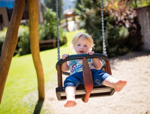 Cute little boy on the swing at the playground.