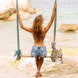 beautiful-woman-on-swing-in-tropics-T5BDGJZ