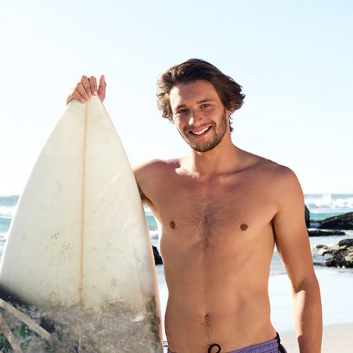 surf-guy-standing-with-surfboard-at-the-beach-P3E48SA