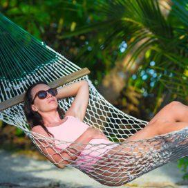 Woman relaxing on hammock sunbathing on vacation