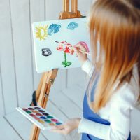 Cute little girl in a blue apron. Child painting at home