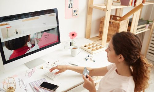 Young woman in tshirt sitting at table and entering number of credit card on website while buying goods on internet