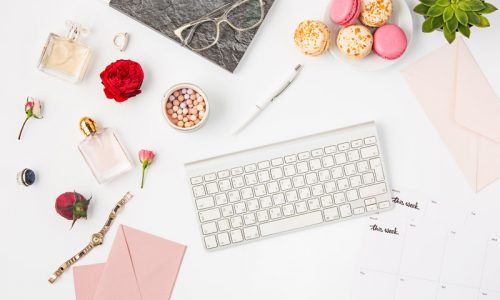 Top view of white female office table with pc keyboard, notebook, pen on white