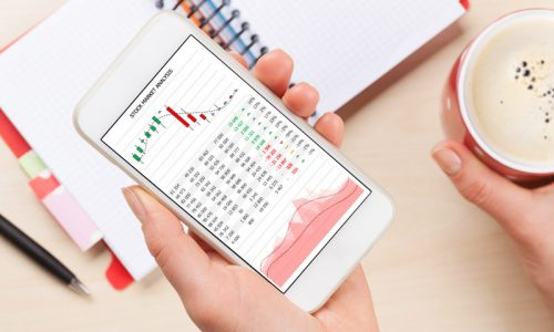Woman holding smartphone with stock market analytics app above business desk. Top view