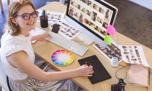 Portrait of young Caucasian female graphic designer working on graphic tablet at desk in office. She is smiling and looking at camera