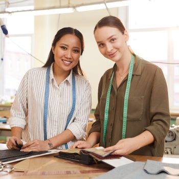 Portrait of multiethnic couple of fashion designers smiling at camera while working with patterns of fabrics in workshop