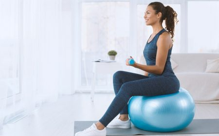 Active Hispanic lady with dumbbells sitting on fitness ball at home, copy space