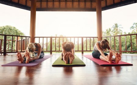 Three women doing yoga together at class, practicing paschimottanasana pose. Fitness females stretching forward in yoga.